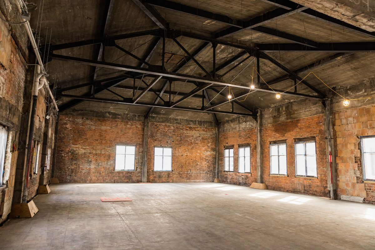 A large open room with red brick walls and steel beams on the ceiling.