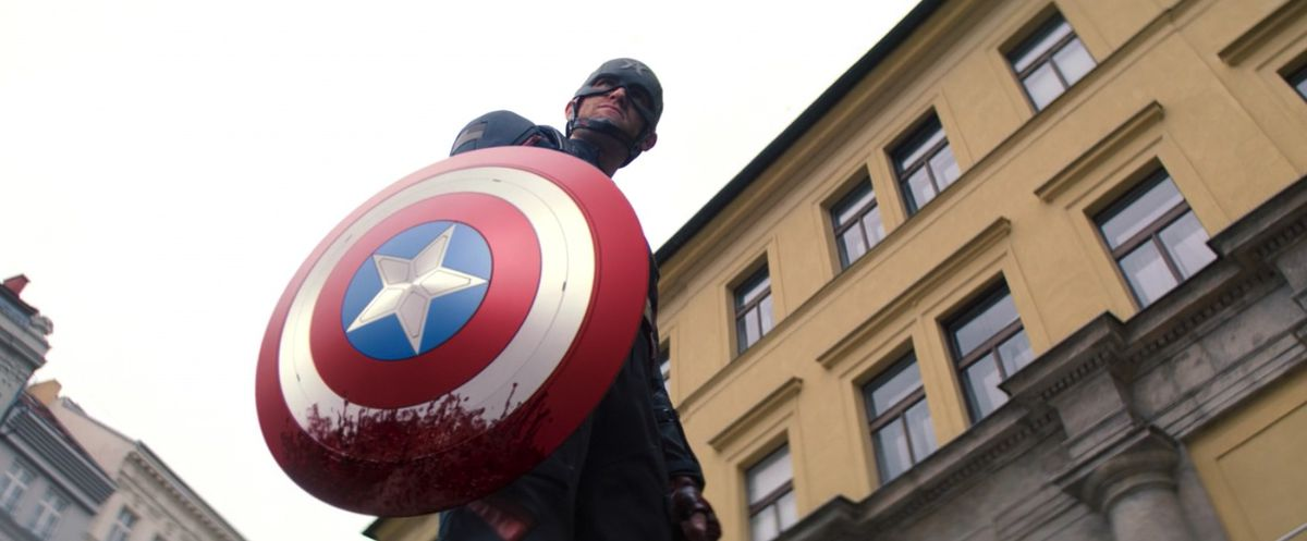 Captain America aka John Walker holds a bloody Captain America shield in Falcon and the Winter Soldier