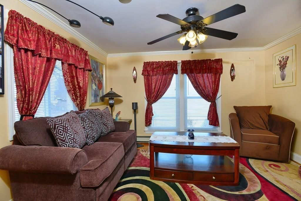 A corner living room with a couch facing a large coffee table, and there's a ceiling fan.