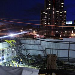 Emergency personel remove an injured man from the site of a crane collapse where construction is going on for the 7 line subway extension Tuesday, April 3, 2012, in New York. Fire officials say a crane collapse at a Manhattan construction site has injured two people.