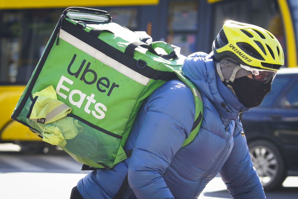 A Uber Eats delivery cyclist is seen wearing a face mask in Warsaw, Poland on March 23, 2020. Polish government spokesman Piotr Muler on Monday announced the administration would not rule out further expanding restrictions to prevent the spread of the coronavirus.