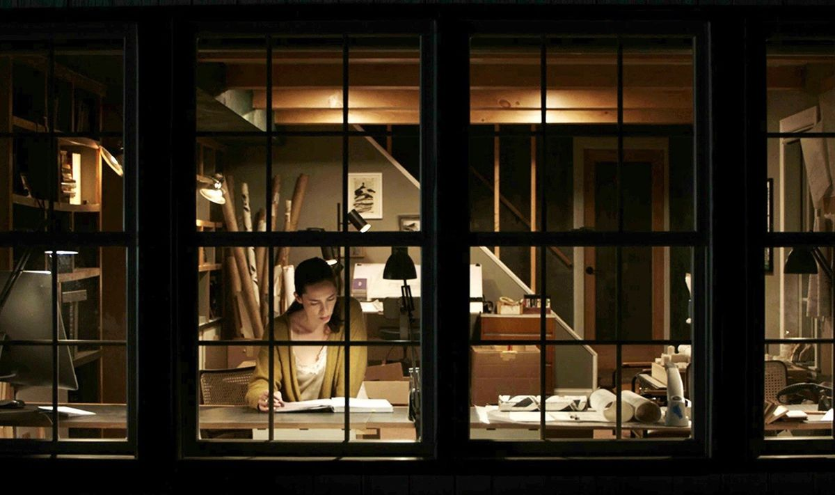 Rebecca Hall in The Night House, seen in the dark through a series of windows, from outside her house