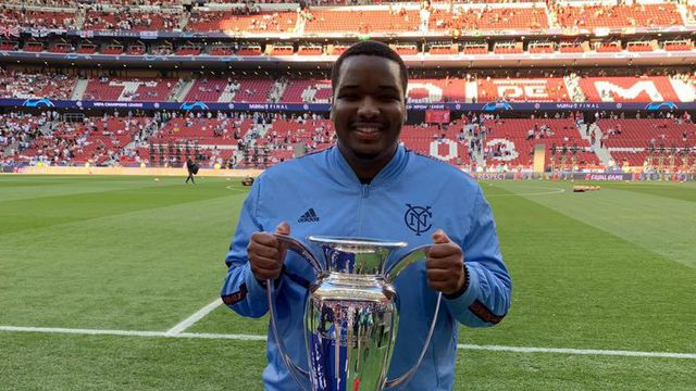 Chris Holly on the sideline of a soccer stadium holding the Champions League cup