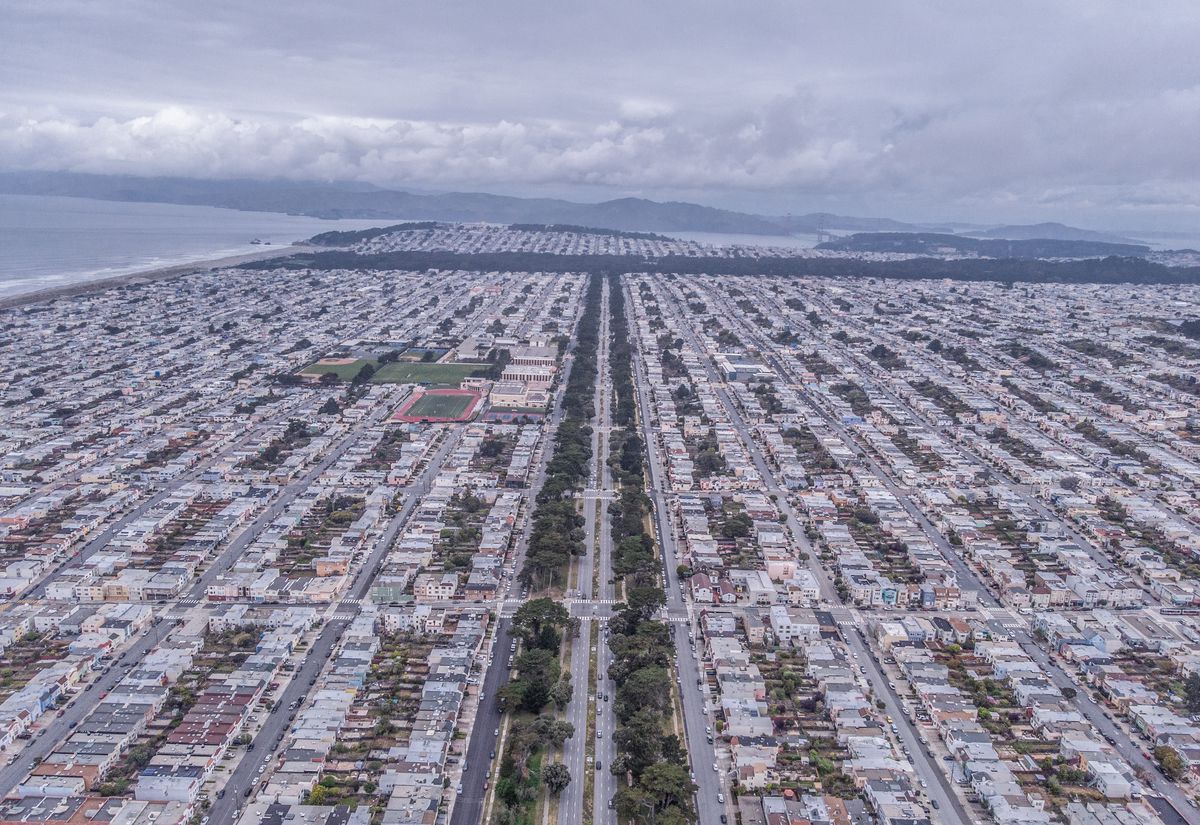 Aerial view of small homes lined up for blocks. A tree-lined avenue cuts through them all.