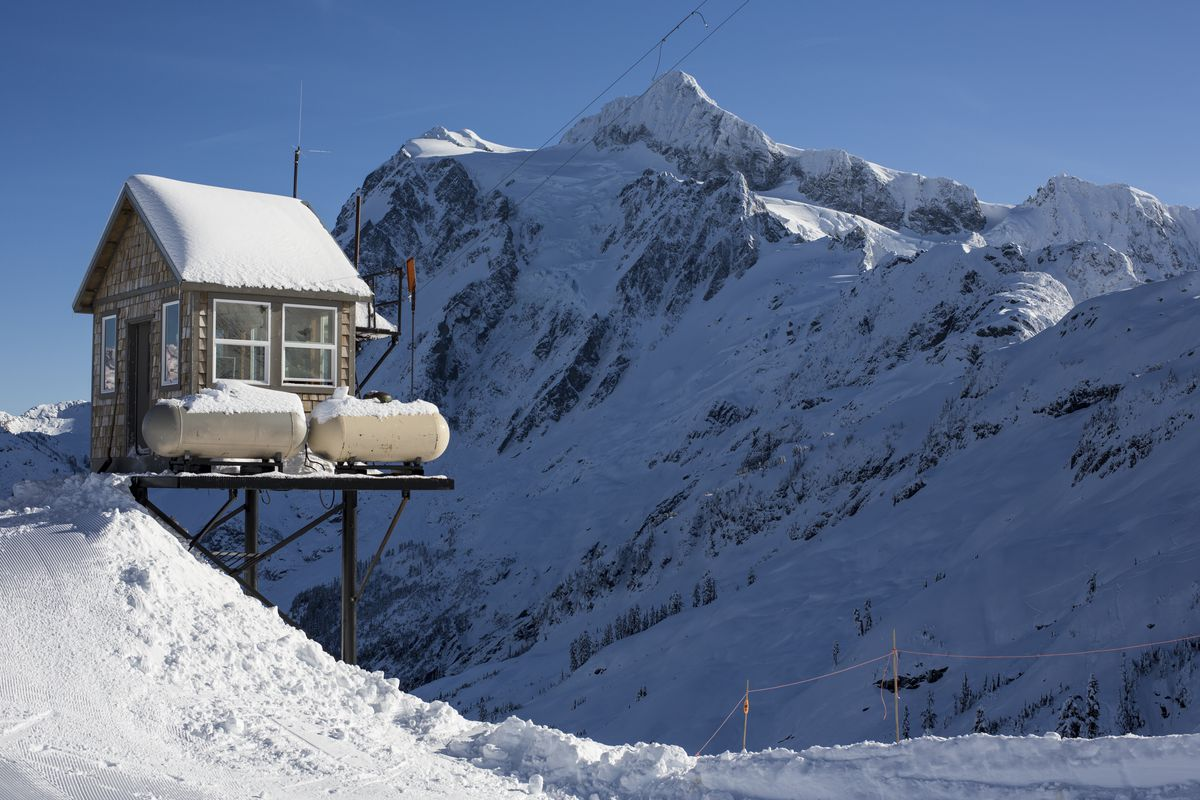 A small cabin-like house is partially up on stilts looks out on a snowy mountainside, with another snowy mountain in the background.