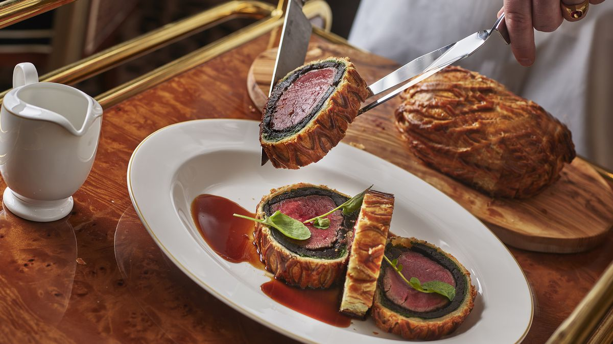 A sliced beef Wellington on an oval white plate with hands holding a slice in two knives