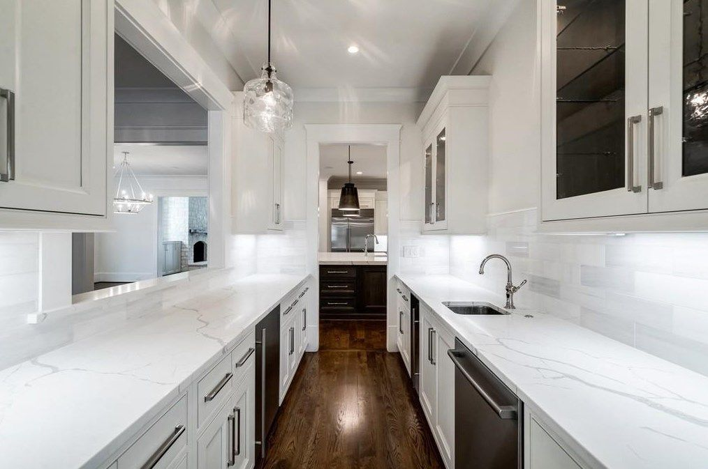 A long white galley kitchen with glass cabinets.