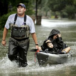 People evacuate a neighborhood inundated by floodwaters from Tropical Storm Harvey on Monday, Aug. 28, 2017, in Houston, Texas.