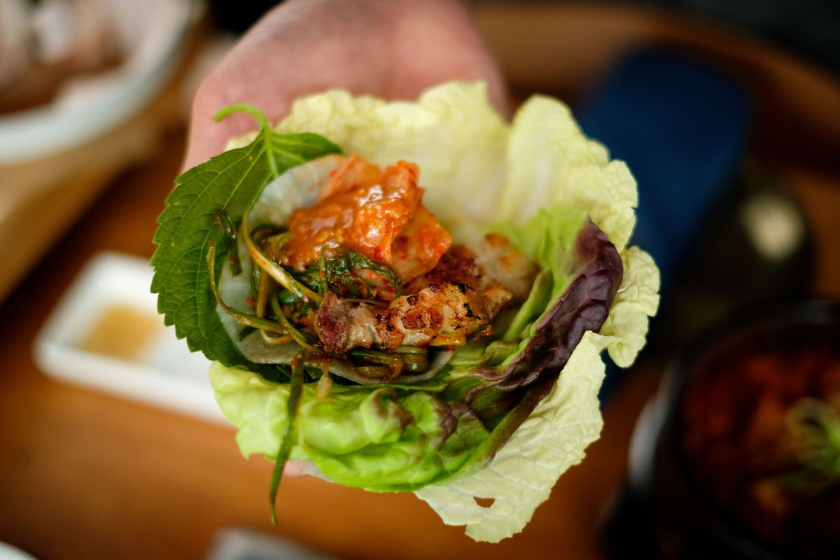 A lettuce wrap with kimchi and pork.