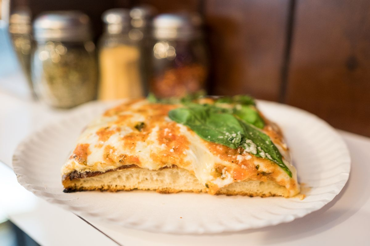 A slice of pizza garnished with basil, laid on a white paper plate