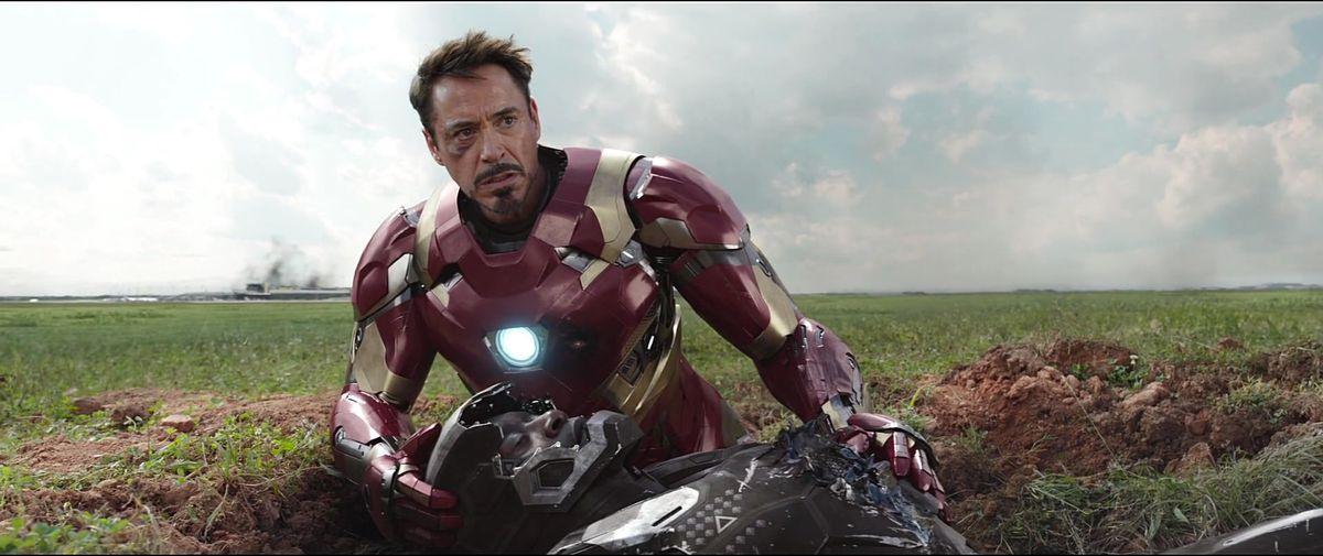 Iron Man holding a dying war machine in CAPTAIN AMERICA: CIVIL WAR