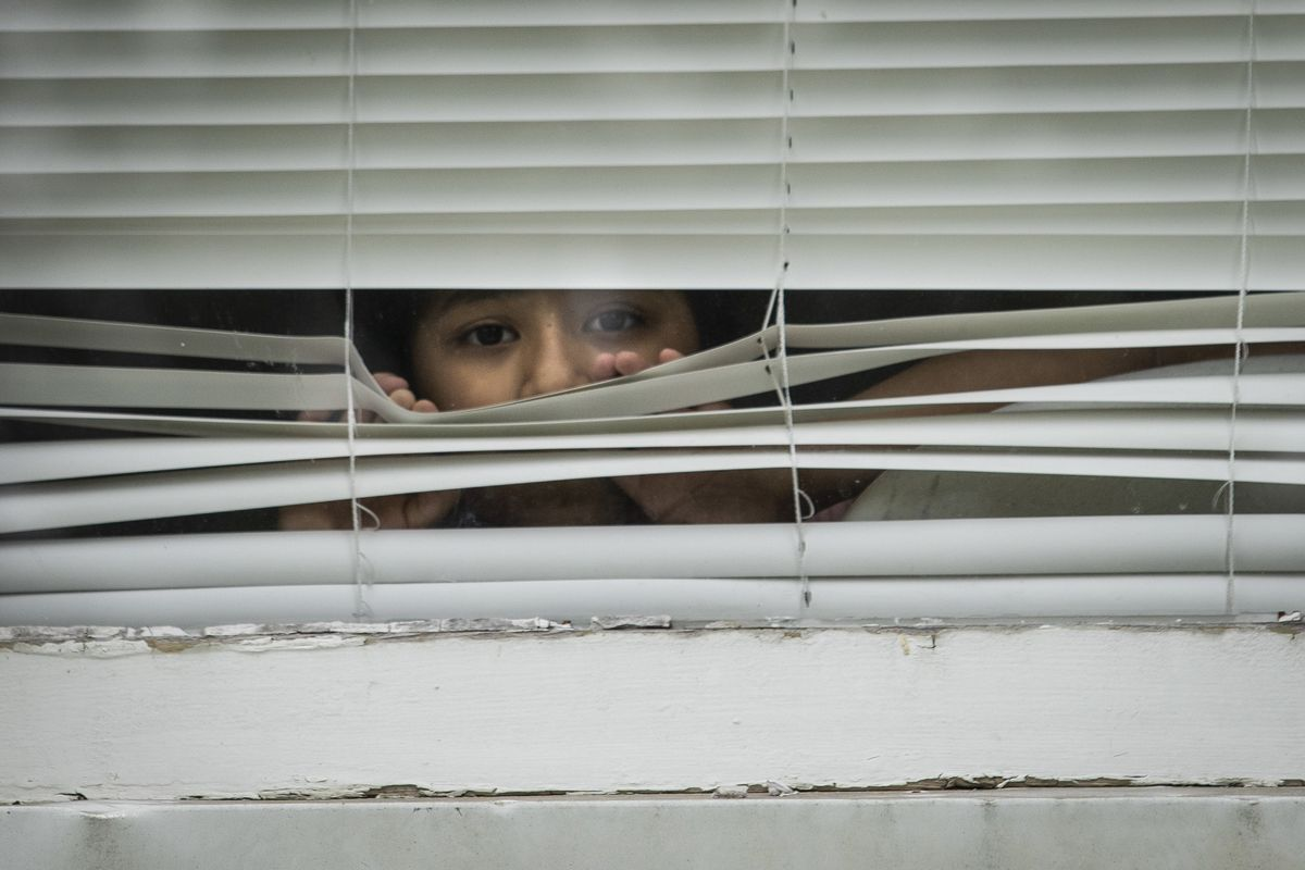 Rebecca Aviles, 7, peeks out the window of her family's Maywood home, Thursday afternoon, May 28, 2020.
