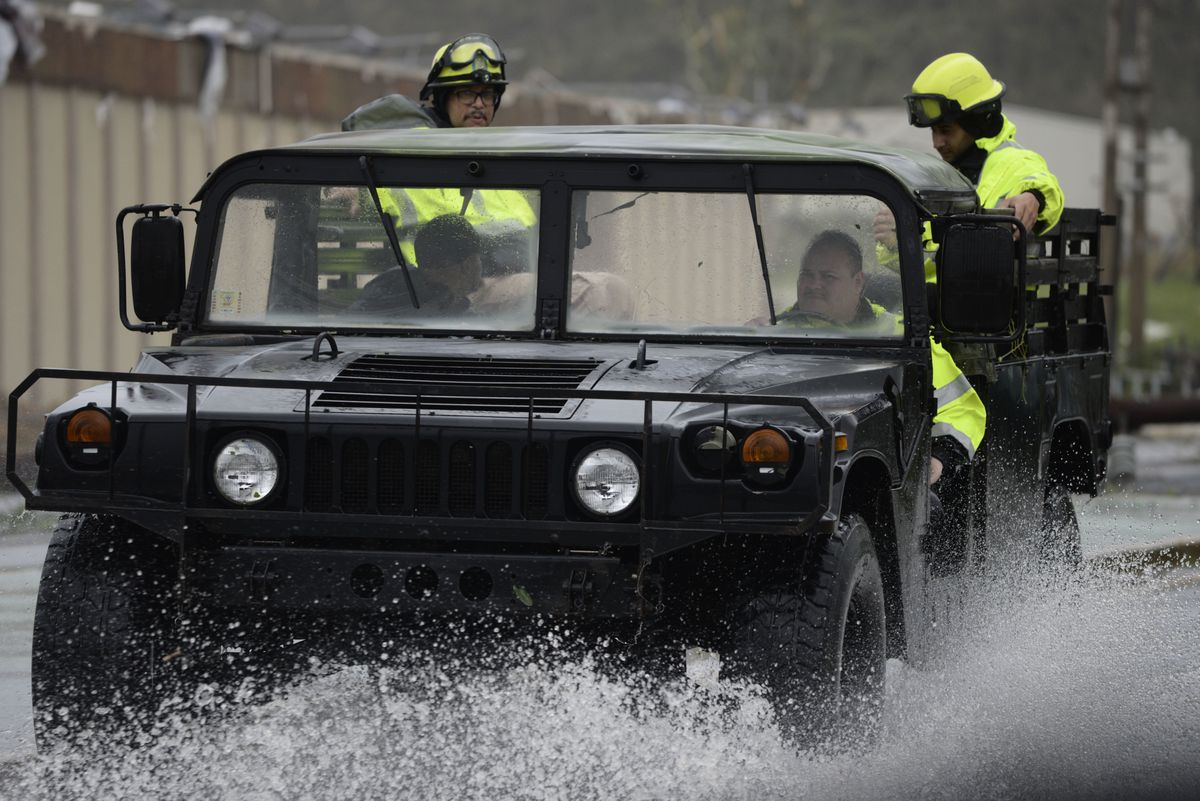 Rescue personnel from the Emergency Management Agency drive through a flooded road after Hurricane Maria hit the eastern region of Puerto Rico.   Carlos Giusti/Associated Press