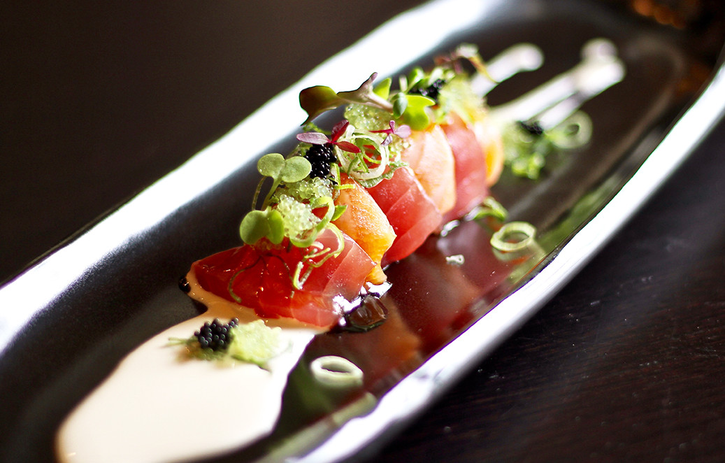 Several pieces of sashimi sit on a long plate at Fuji at Ink Block in Boston's South End