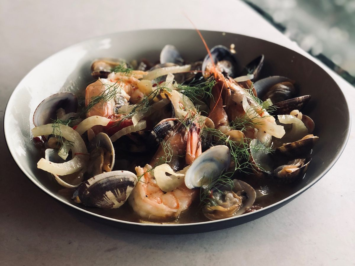 A wide, shallow bowl of cooked mussels, onions and, other fixings on a sun-lit countertop