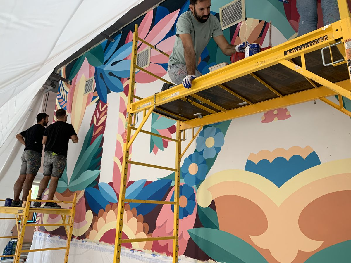 Two muralists working on the mural for Buena Vida with a third person painting from yellow scaffolding
