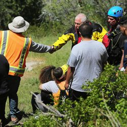 A relative of a 22-year-old hiker who fell in Bell Canyon shakes hands with a member of the Salt Lake County Search and Rescue team on Monday, June 5, 2017, as crews tried to recover the body. Siaosi Brown's body was spotted in the lower falls of the canyon. His body was trapped on some logs in the middle of the waterfall, Unified Police Lt. Brian Lohrke said.