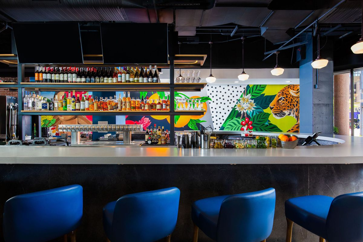 A wraparound bar at the Freshman sits in front of a colorful mural sporting a leopard and coffee plants