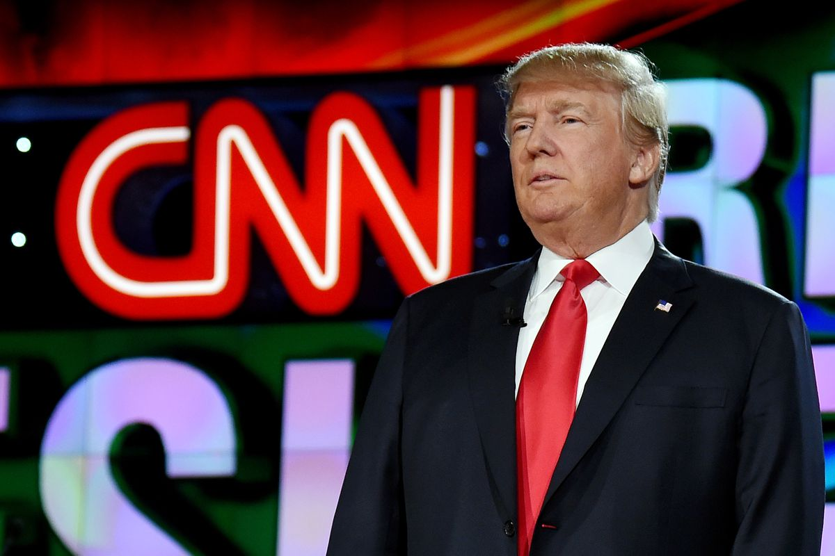 Presidential candidate Donald Trump stands in front of a sign with the CNN logo.
