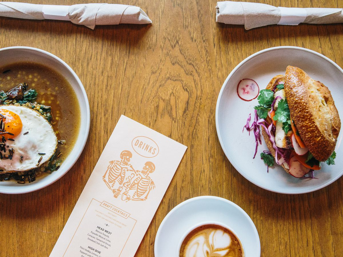 Two plates of food, one with a sunny-side-up egg and a broth and a sandwich on the other, with a cup of a latte on a wooden table