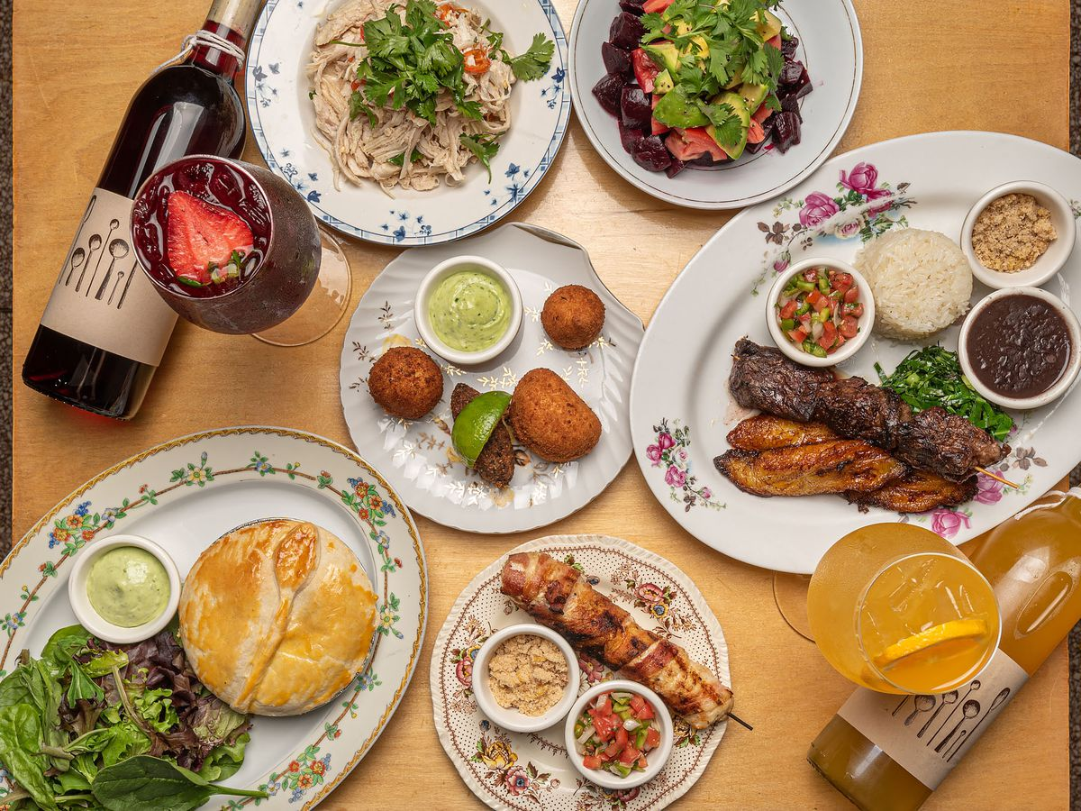 Various Brazilian dishes at Wood Spoon on decorated plates, sangria, and wine bottles.