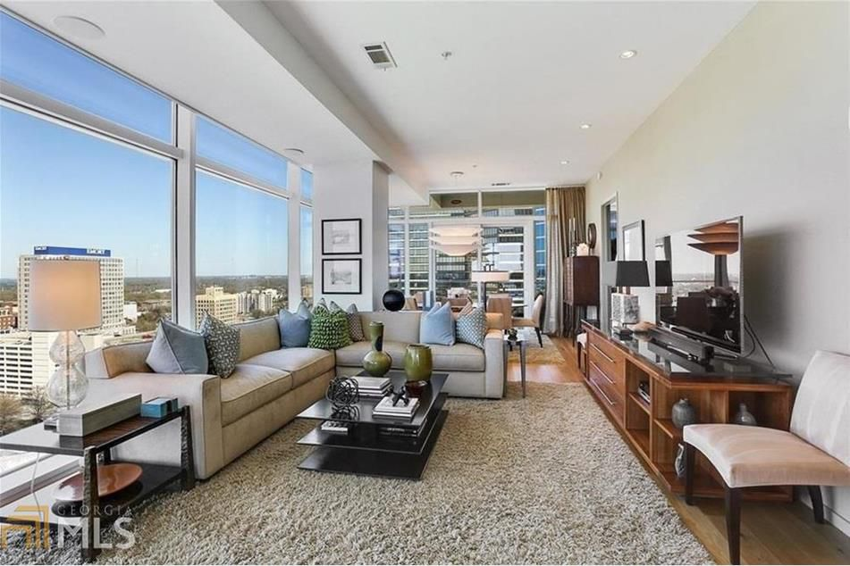 a large living room in a condo with a big couch and views.