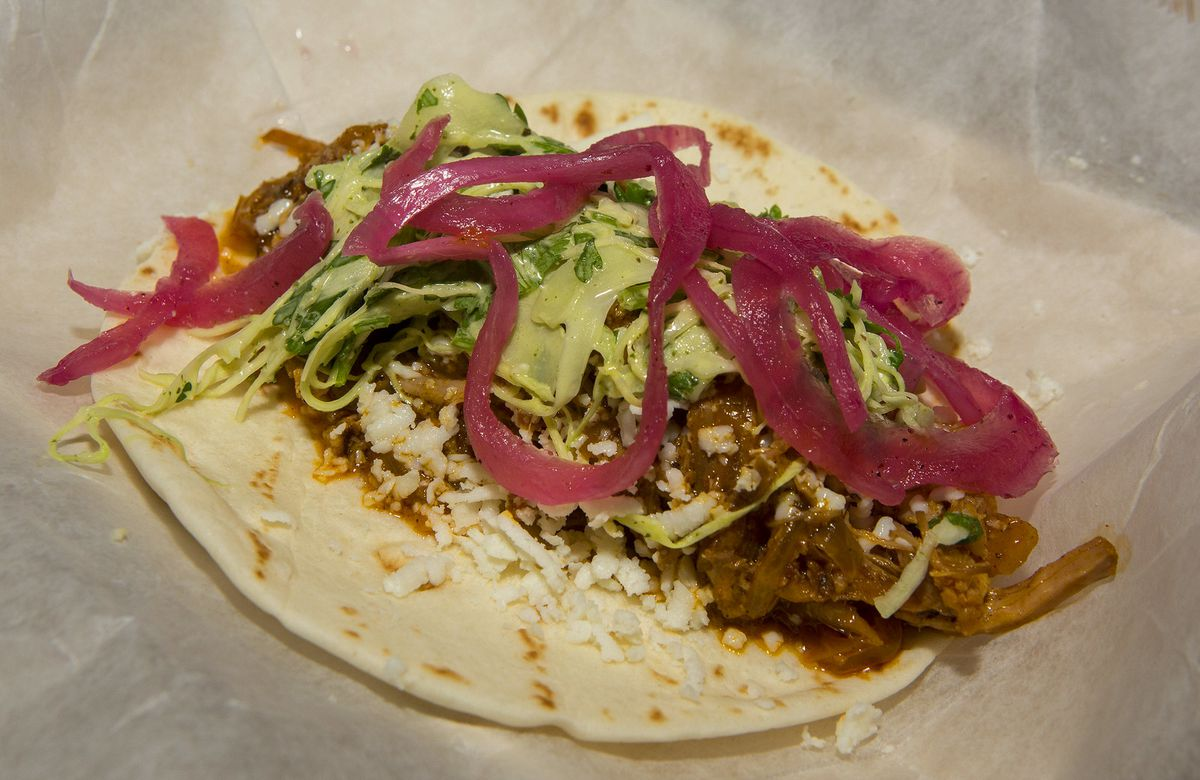 A flour taco with pickled red onions and pulled pork.