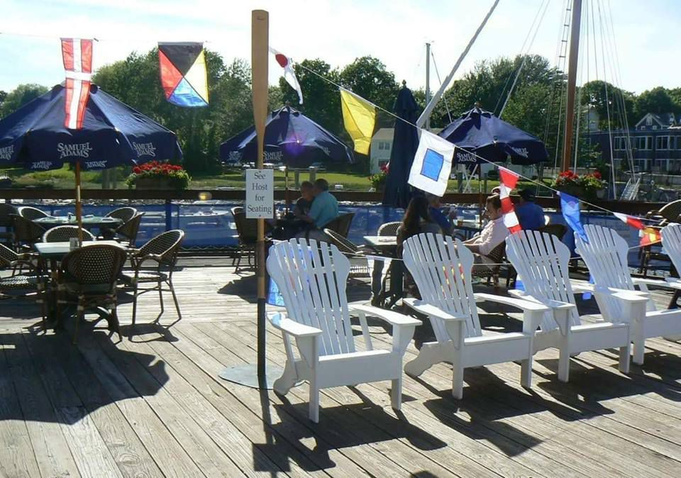 chairs on a patio on the water with nautical flags in the background