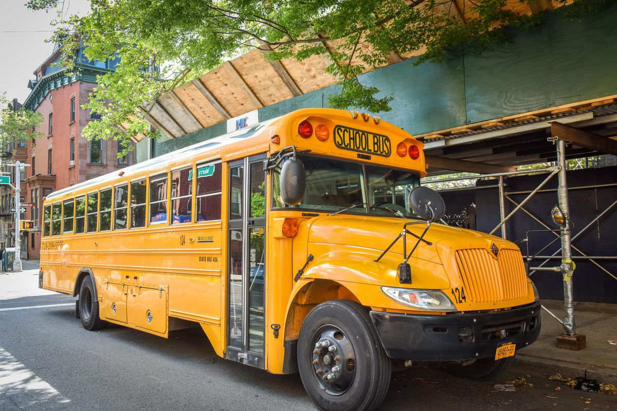 A yellow school bus waits on the street.