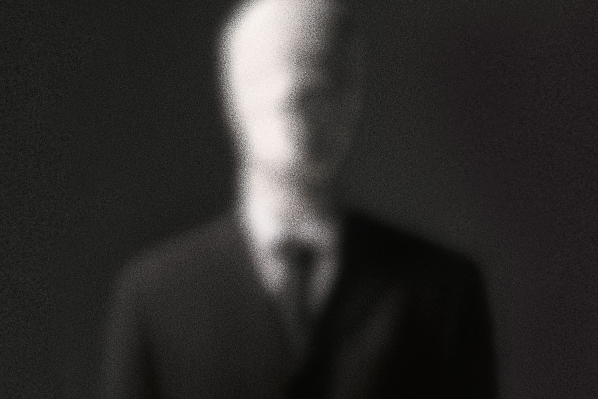 A blurry picture of a faceless man in a black suit and tie, the Slenderman