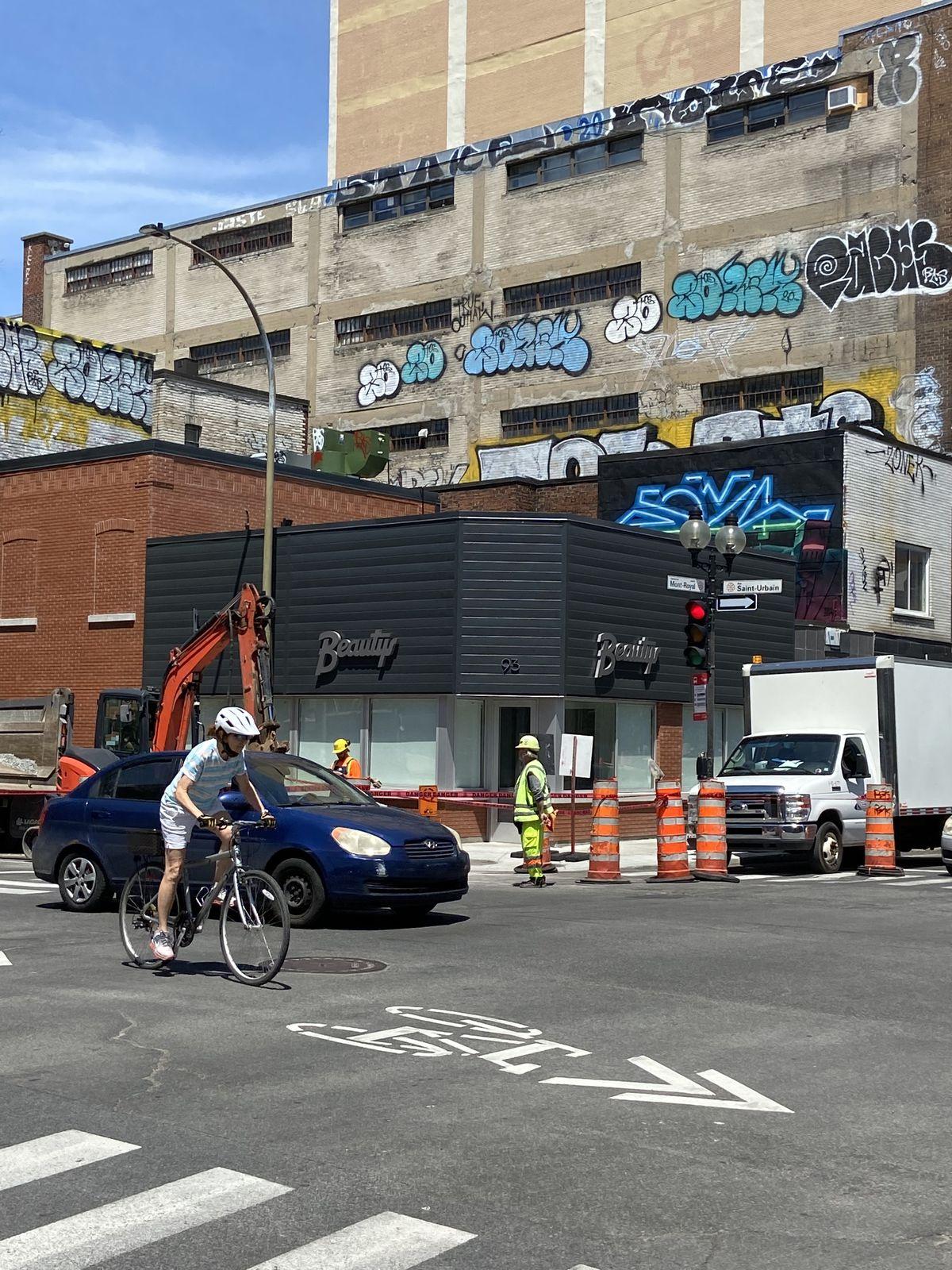 construction cones, cars, bikers in front of Beautys