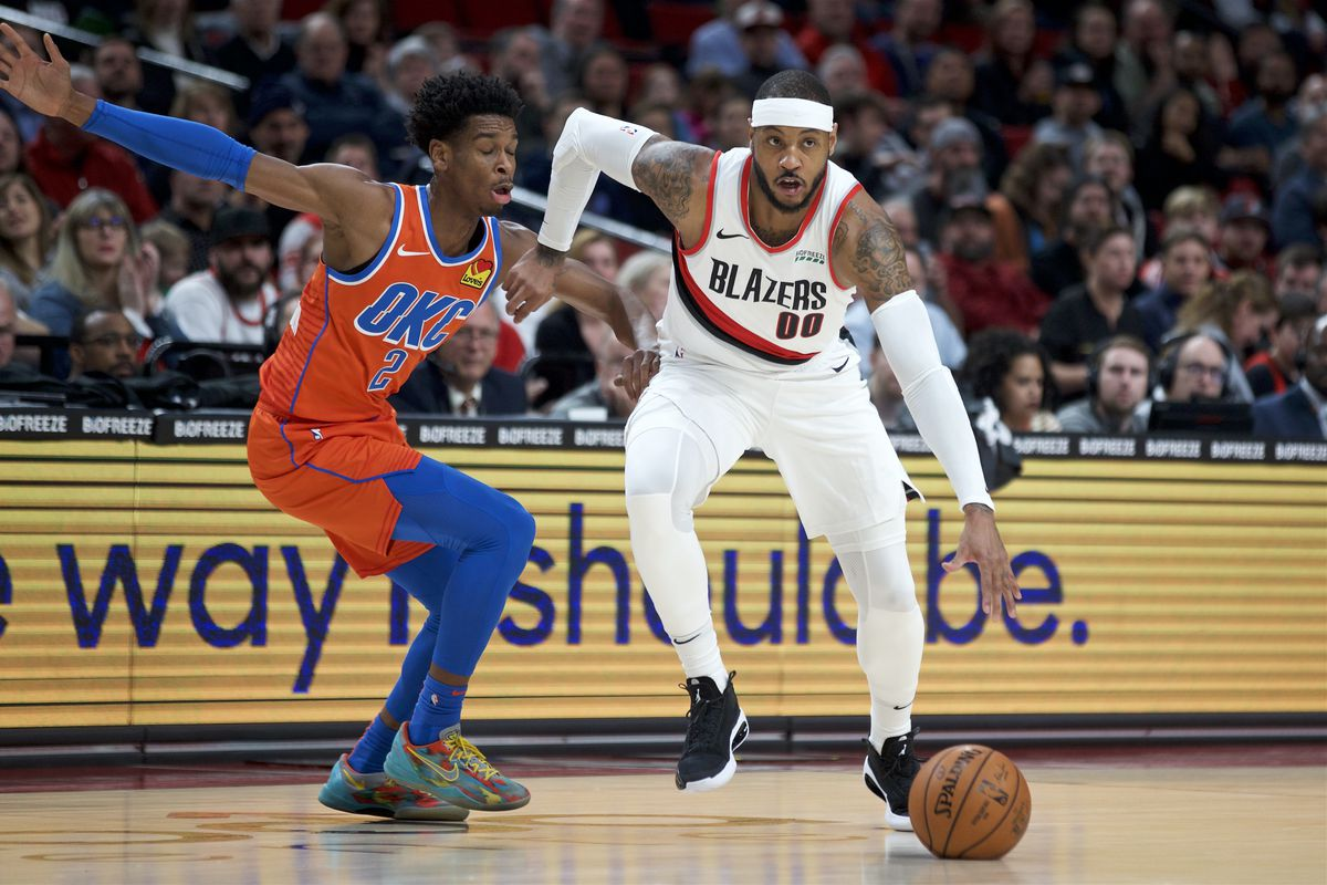 Portland Trail Blazers forward Carmelo Anthony dribbles past Oklahoma City Thunder guard Shai Gilgeous-Alexander during the first quarter at the Moda Center.