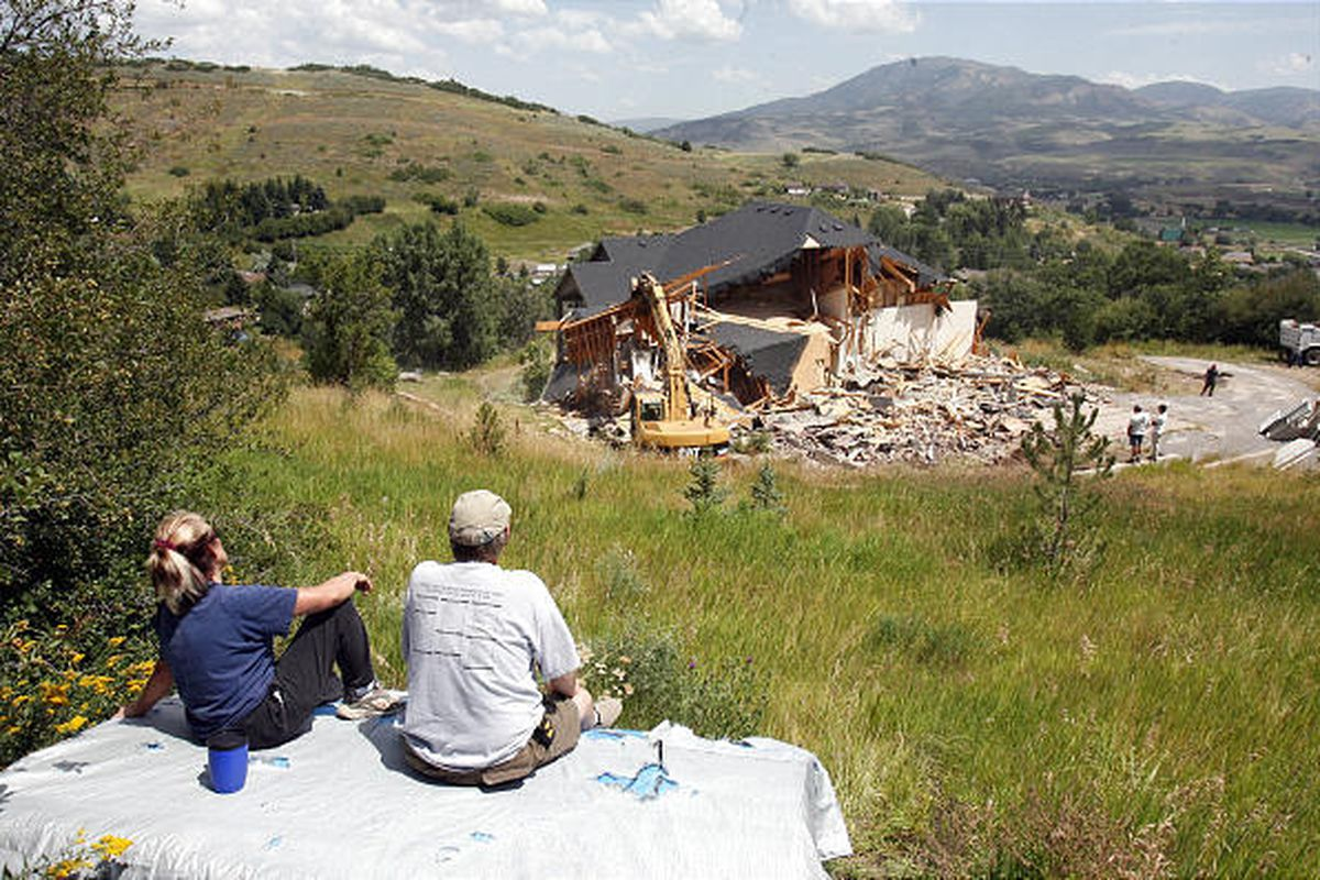 Sharon and Cecil Litle watch as crews demolish a condemned home in Mountain Green.