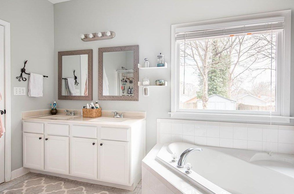 A white master bathroom with a small vanity at left.