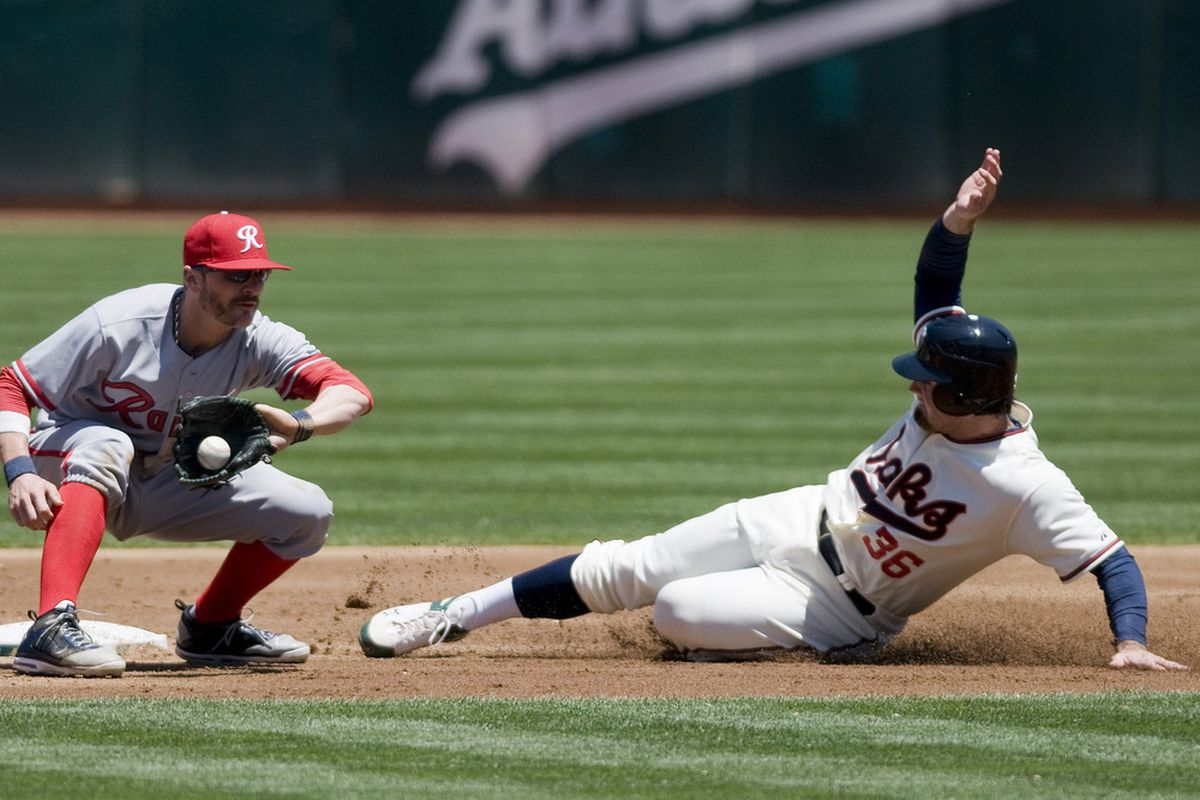 July 8, 2012; Oakland, CA, USA; Seattle Mariners shortstop Brendan Ryan (26) attempts to tag out Oakland Athletics catcher Derek Norris (36) as he slides into second base at O.co Coliseum.  Mandatory Credit: Ed Szczepanski-US PRESSWIRE