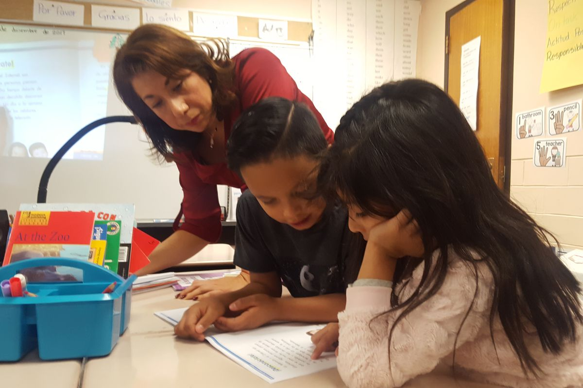 First grade teacher Nancy Carbajal at Dupont Elementary School in Adams 14 listens as students practice reading in Spanish. (Photo by Yesenia Robles, Chalkbeat)