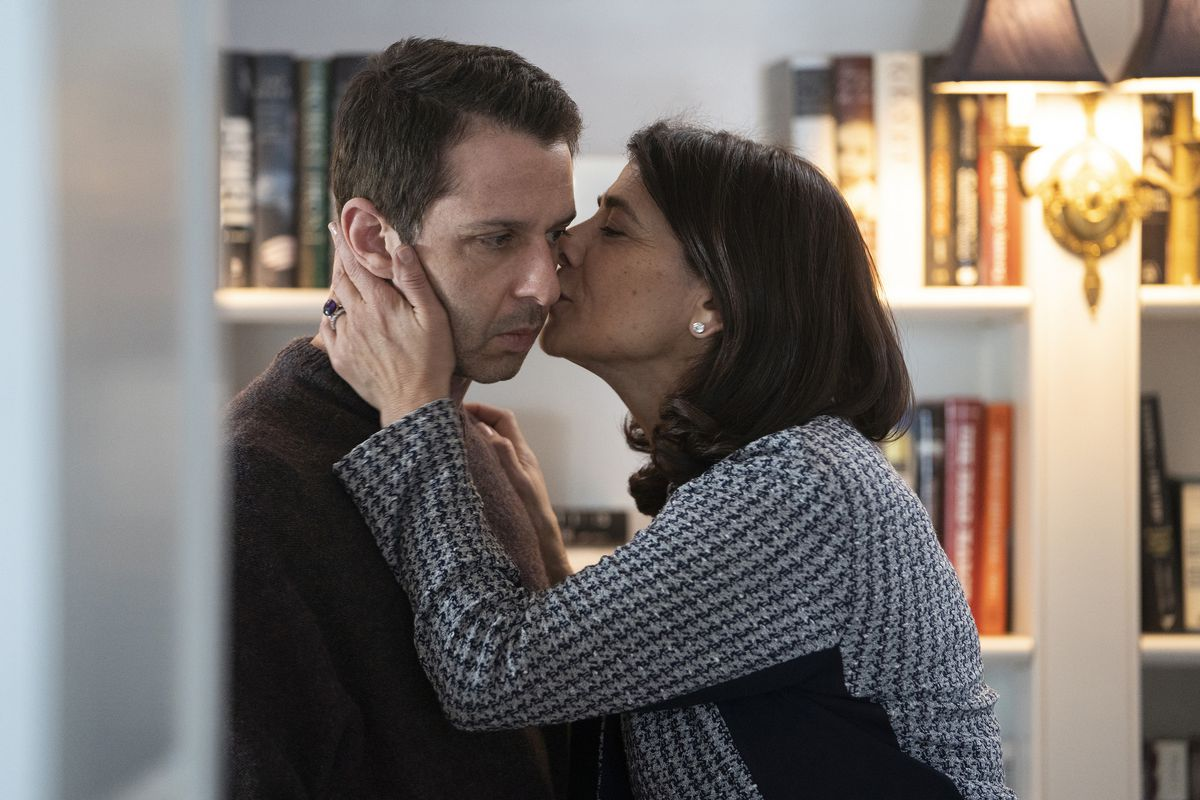 on Succession, Kendall looks unemotional as his mother-in-law, Marcia, kisses him on his left cheek