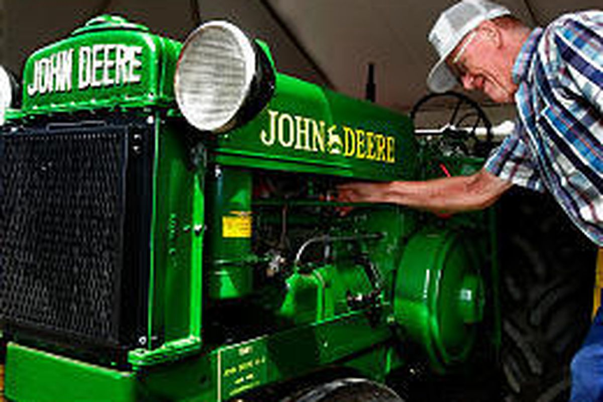 Bud Robinson of Jacksonville, Ill., inspects a mint condition vintage 1941 John Deere tractor in August.