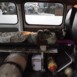 In this Wednesday, Aug. 22, 2012 photo, head trauma patient Sabir Khan, 35, lies unattended in an ambulance outside a hospital in New Delhi, India. Most ambulances in India are upgraded vans or mini-buses with just a stretcher, an oxygen cylinder and no paramedic.