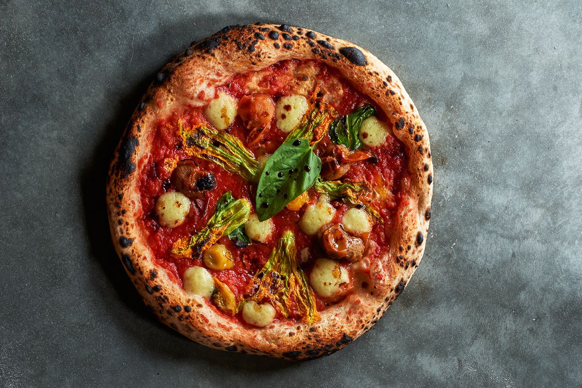 Overhead view of a pizza on a gray background. The pizza's crust is dotted with spots of char, and there are blobs of cheese and a large piece of basil, as well as some other green vegetables.