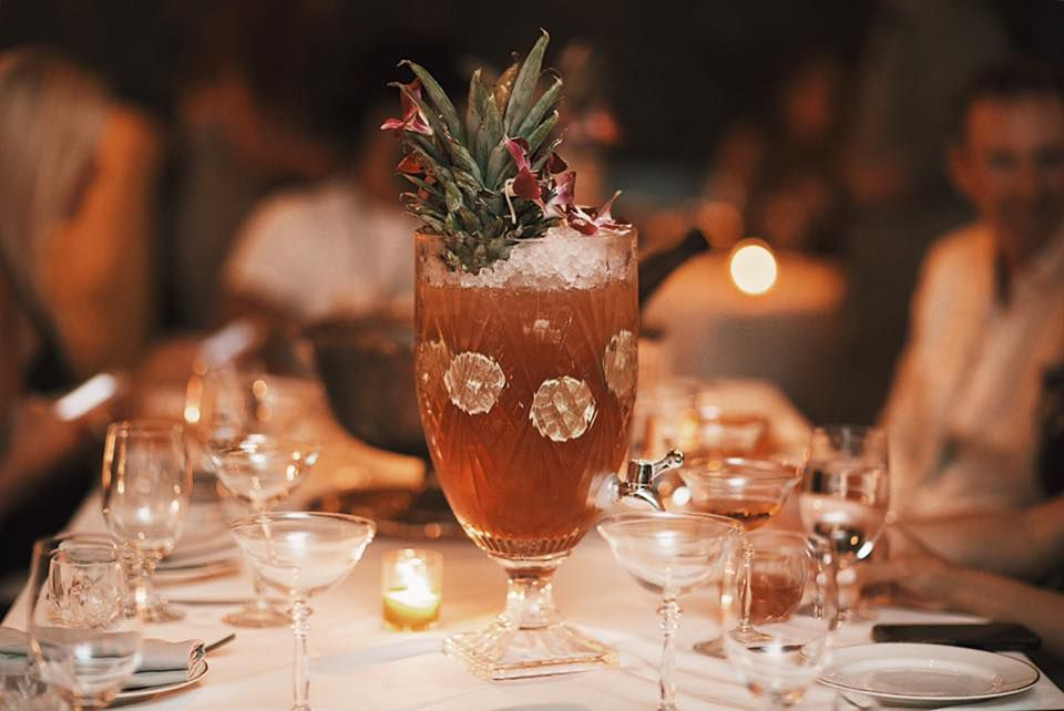 A large-format cocktail is served in an elegant glass vessel with a spout on a white tablecloth-covered table in a dimly lit restaurant. There are citrus slices in the drink, and pineapple leaves are coming out of the top of it.