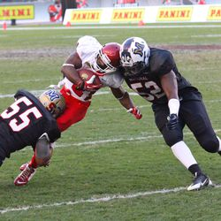 Roy Finch is tackled by Stephon Robertson (#55) and Jesse Joseph (#52).