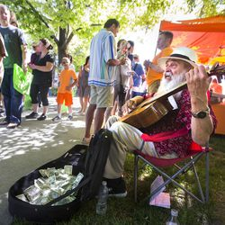 Anastacio Castillo sings for money as shoppers take in the opening day of the farmers market Saturday, June 13, 2015, in Salt Lake City at Pioneer Park.