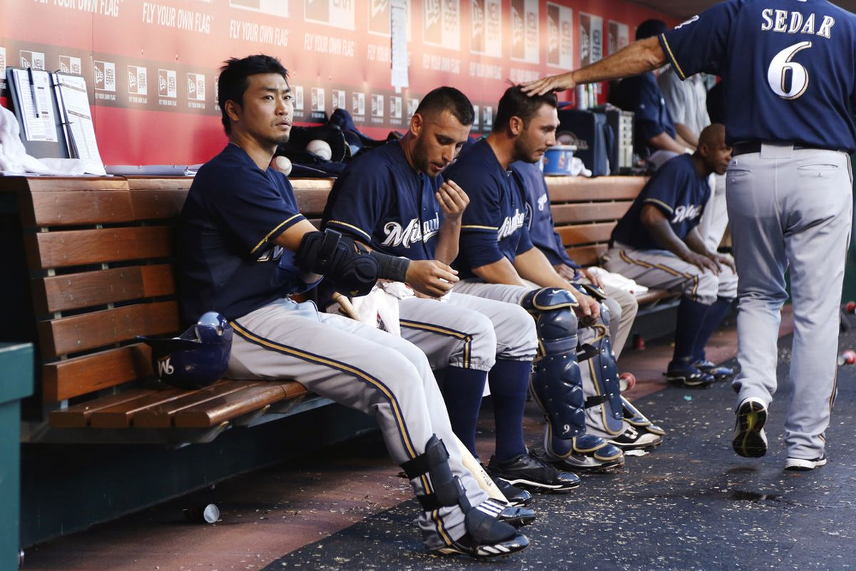 CINCINNATI, OH - JUNE 26: Norichika Aoki #7 of the Milwaukee Brewers gets ready in the dugout during the game against the Cincinnati Reds at Great American Ball Park on June 26, 2012 in Cincinnati, Ohio. (Photo by Joe Robbins/Getty Images)