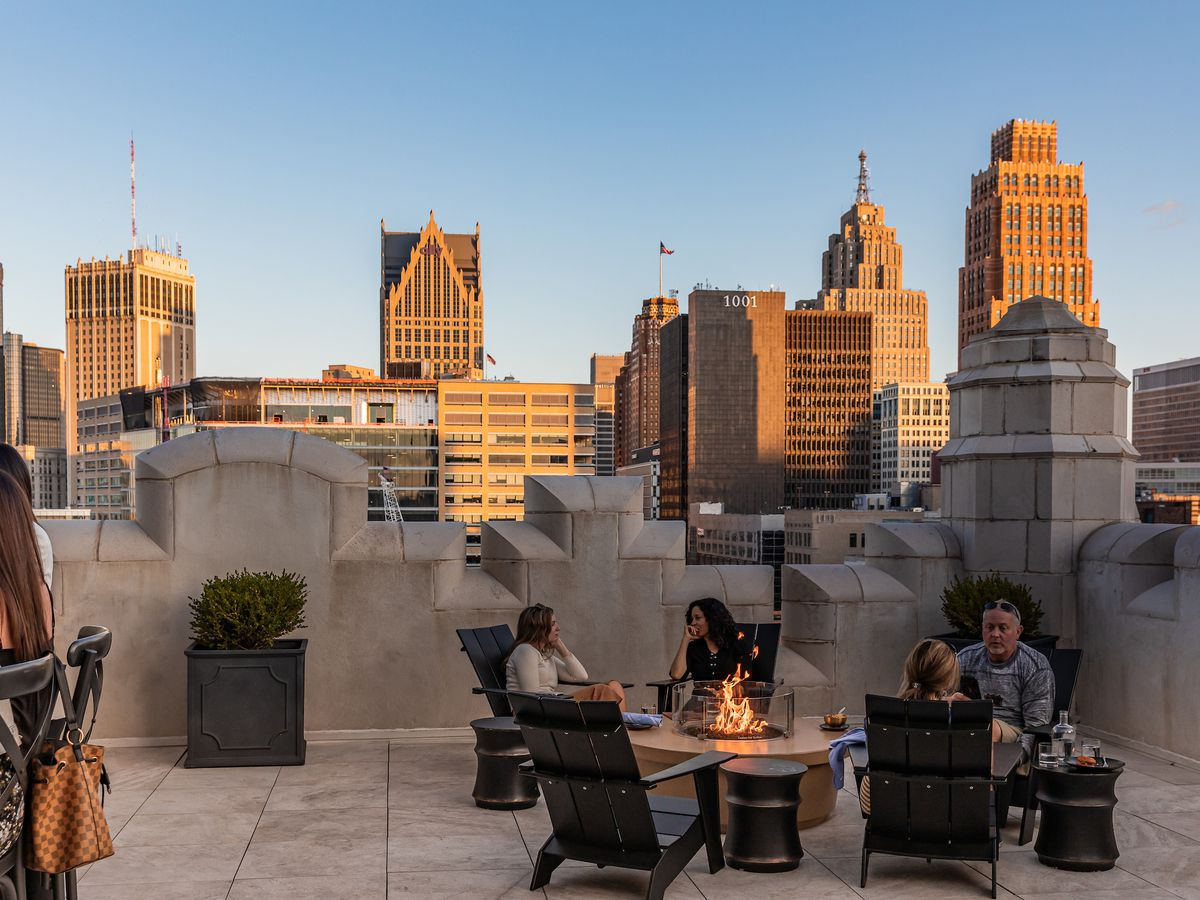 Customers sit around a fire pit on the roof of the Monarch Club on a sunny afternoon.