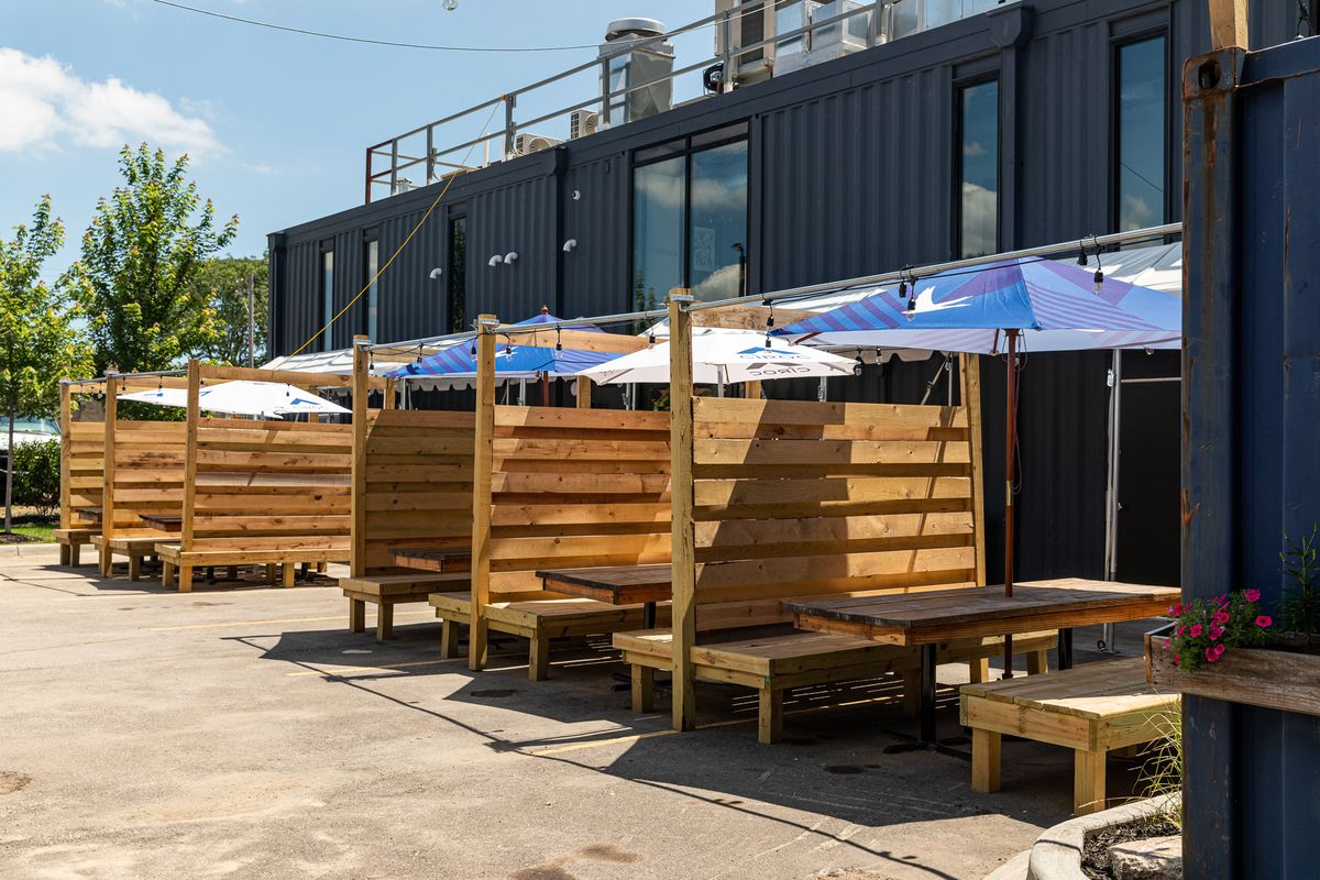Wooden cabins with extremely high wooden backs are covered with umbrellas on a sunny day.