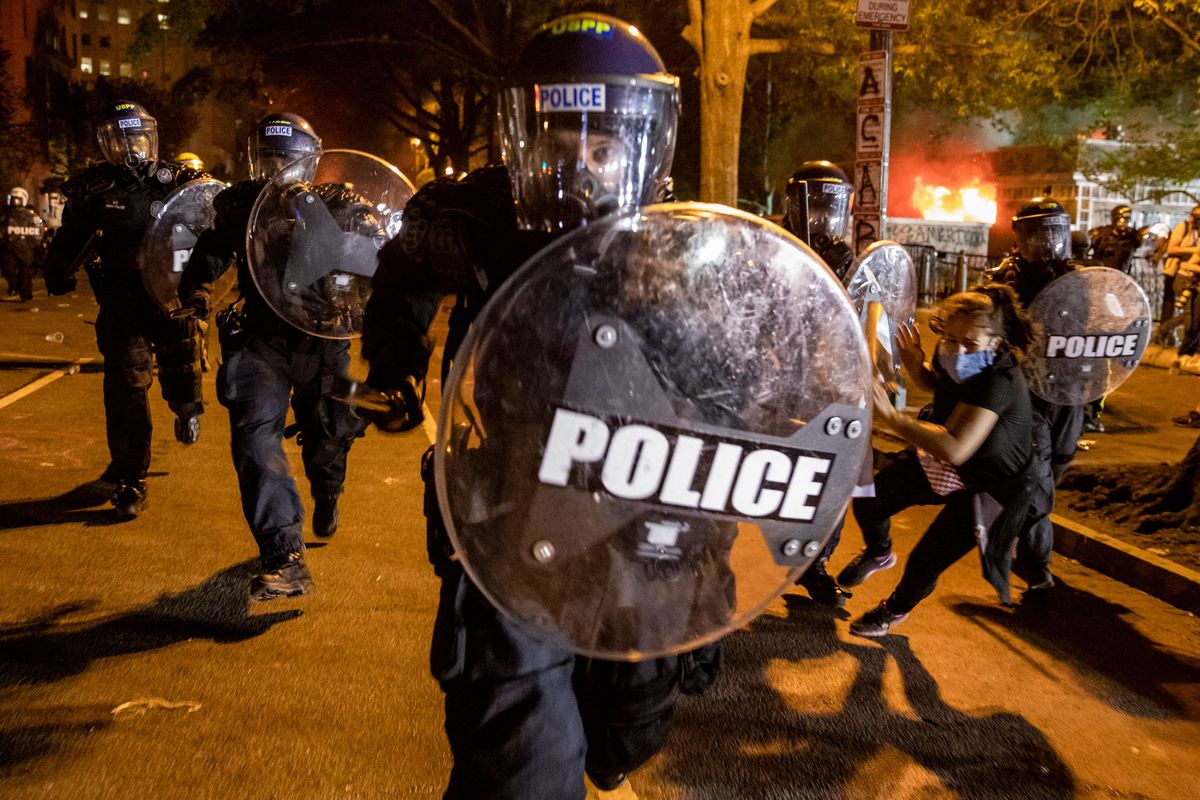 A officer in black riot armor lunges toward the photographer, truncheon arm raised and clear riot shield held high. Behind this officer, two others in riot armor run forward, as if about to charge an enemy in battle, as a third officer appears to strike a protester attempting to flee.
