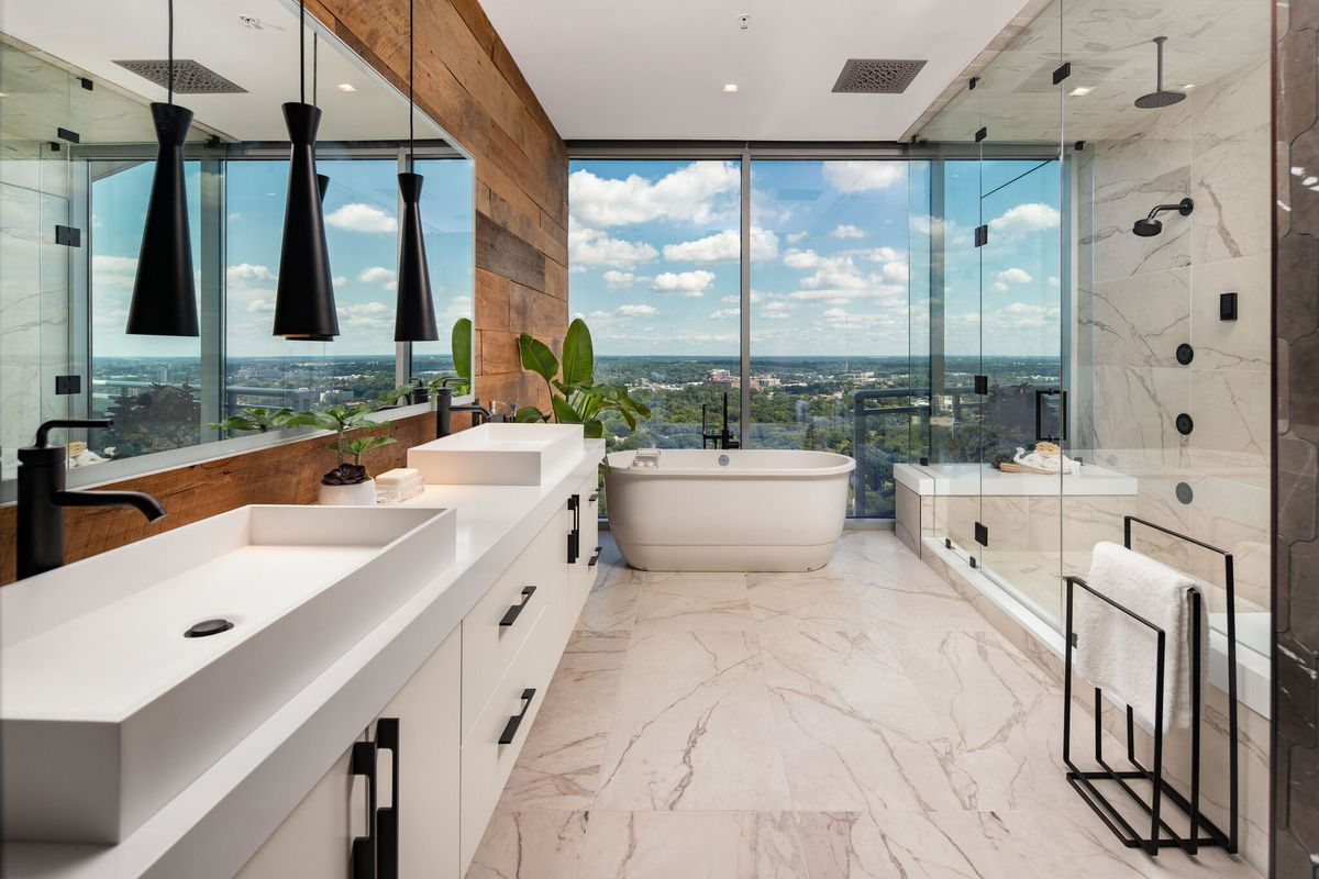 A white marble master bathroom with a recclaimed wood on one wall.