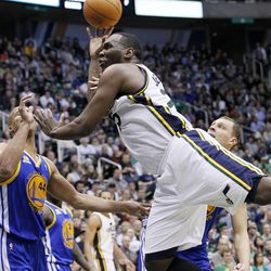 Utah Jazz center Al Jefferson, center, is fouled by Golden State Warriors center Andris Biedrins, right, of Latvia, as small forward Richard Jefferson (44) also defends during the second half of an NBA basketball game, Friday, April 6, 2012, in Salt Lake City. The Jazz won 104-98.  (AP Photo/Colin E Braley)