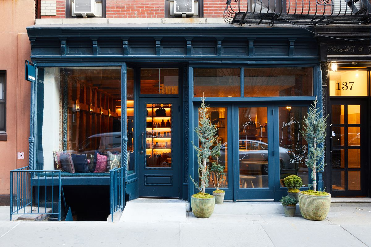 Small trees and potted plants sit in front of a swanky Soho diner. The front of the restaurant is painted blue with warm shining through windows from the inside.